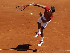 Roger Federer of Switzerland follows through on a serve during his victory Wednesday against Maxime Teixeira of France in the second round of the French Open.