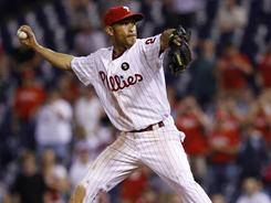 Wilson Valdez delivers during his scoreless 19th inning against the Reds. Valdez became the first position player to register a pitching win since 2000.