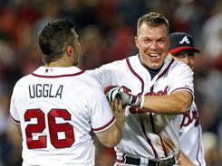 The Braves' Chipper Jones, right, celebrates with teammate Dan Uggla after driving in the the gam e-winning run in the 12th inning against the Reds. Atlanta won 3-2.