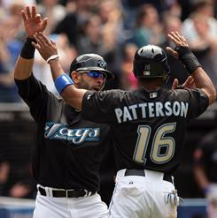 Toronto Blue Jays right fielder Jose Bautista celebrates with designated hitter Corey Patterson after scoring on a double by Juan Rivera in the 7th inning against the Chicago White Sox in Toronto.