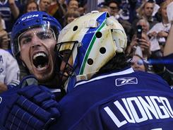 Alex Burrows is ecstatic as he celebrates the Canucks' clincher with goalie Roberto Luongo.
