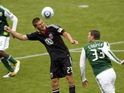 D.C. United's Perry Kitchen, left, heads the ball over the Portland Timbers' Kenny Cooper during the first half of their MLS game in Portland, Ore. DC United won 3-2 .