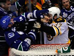Alex Burrows, left, and Patrice Bergeron battle behind the net Wednesday. Bergeron says Burrows bit down on his finger.