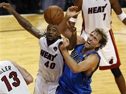 The Heat's Udonis Haslem, left, and the Mavericks' Dirk Nowitzki go after a loose ball during the second half of Game 1. The Heat outrebounded the Mavs 43-36, 16-6 on the offensive boards.