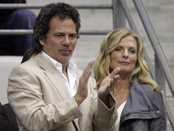 Tom Gores, left, with wife Holly, applauds the Pistons during an April game against the Cavaliers. Gores' purchase of the Pistons was completed Wednesday.