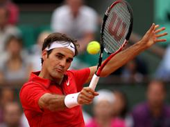Roger Federer of Switzerland hits a volley Friday during his four-set viictory against Novak Djokovic of Serbia in the semifinals of the French Open. Federer ends Djokovic's unbeaten streak in 2011.