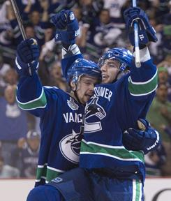 Canucks left wing Alex Burrows, right, celebrates with Mason Raymond after scoring a first-period goal against the Boston Bruins during Game 2 of the NHL finals in Vancouver.