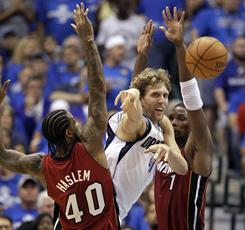 Dallas Mavericks forward Dirk Nowitzki passes between Miami Heat center Udonis Haslem and forward Chris Bosh during Game 3 of the NBA Finals in Dallas.