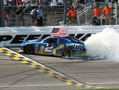 Brad Keselowski celebrates winning Sunday's STP 400 with an American flag and a burnout at Kansas Speedway.