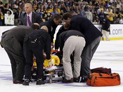 Boston Bruins right wing Nathan Horton is carted off the ice after being injured on a hit by Vancouver Canucks defenseman Aaron Rome during the first period.