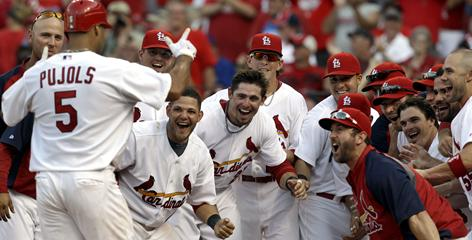 Teammates wait to congratulate Albert Pujols after one of his two walk-off home runs against the Cubs this weekend. Pujols had gotten off to a slow start this season for the injury-depleted Cardinals.