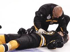 Boston Bruins right wing Nathan Horton is tended to by a trainer after a hit by Vancouver Canucks' Aaron Rome in the first period Monday.