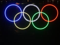 People stop to look at a  tall set of Olympic rings after being illuminated in the harbor outside the Vancouver Convention Centre.