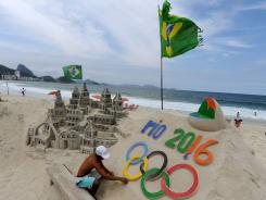 A sculptor works on the Olympic rings on a beach in Rio de Janeiro in October