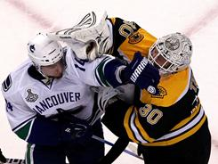Tim Thomas, right, tussles with Vancouver's Alex Burrows late in Game 4.