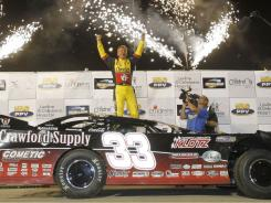 Clint Bowyer celebrates in victory lane after winning the Prelude To The Dream, Tony Stewart's dirt-track race for charity.