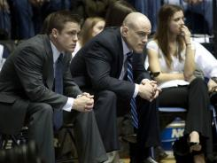 Penn State coach Cael Sanderson, center, and associate head coach Cody Sanderson look on during a Big Ten wrestling dual against Iowa in January.