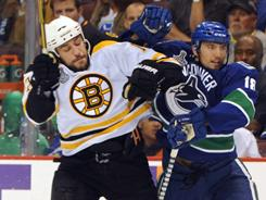 Vancouver's Chris Tanev, right, battles for position with Milan Lucic in Game 5.