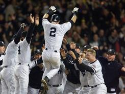 Derek Jeter jumps into the arms of his teammates after hitting a solo home urn in the tenth inning of Game 4 of the 2001 World Series at Yankee Stadium.