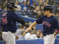Red Sox outfielder Jacoby Ellsbury, right, celebrates with teammate David Ortiz after scoring a run in the ninth inning of Boston's win over the Blue Jays in Toronto. Ellsbury had three hits in the victory.