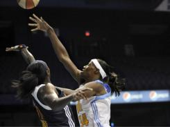 Chicago Sky guard Sylvia Fowles, right, goes up for a shot against the Connecticut Sun's Tina Charles during their game in Rosemont, Ill.