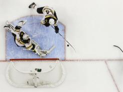 Canucks right wing Maxim Lapierre (40) scores the lone goal of Game 5 past Bruins goalie Tim Thomas, left.