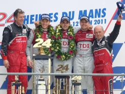 From left, Audi manager Ralf Juttner, Audi No. 2 drivers Benoit Treluyer of France, Andre Lotterer of Germany, Marcel Fassler of Switzerland,  and Audi Motorsport chief Dr. Wolfgang Ullrich react on the podium, after winning the 79th 24-hour Le Mans race in France.