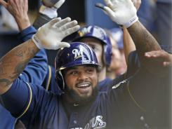 Brewers' Prince Fielder gets high-fives in the dugout after his two-run home run off St. Louis Cardinals pitcher Jake Westbrook.