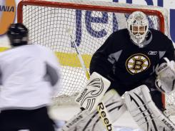 Boston Bruins goalie Tim Thomas takes shots during practice Sunday.
