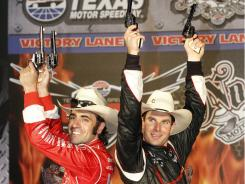 Dario Franchitti, left, and Will Power celebrate in victory lane after splitting wins in the Firestone Twin 275 races Saturday night at Texas Motor Speedway.