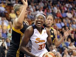 The Sun's Tina Charles, center, powers past the Shock's Elizabeth Cambage, left, while the Shock's Chastity Reed looks on during Connecticut's 90-79 win over Tulsa.