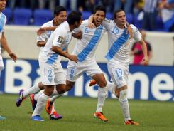 Guatemala defenders Henry Medina (2), Carlos Cabrera (6) and midfielder Jose Del Aguila (19) celebrate a goal against Grenada.