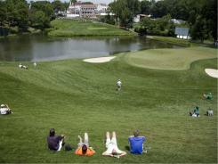 Spectators take up positions near the narrow green for the par-3 10th during practice rounds Monday.