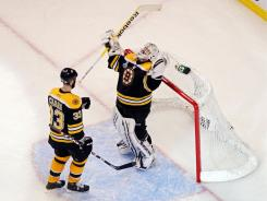 The Bruins' Zdeno Chara (33) celebrates with Tim Thomas (30) after defeating the Canucks in Game 6 of the Stanley Cup Final. Boston defeated Vancouver 5-2 on Monday.