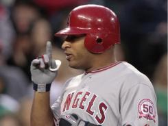 Vernon Wells points skyward as he crosses home plate on his seventh inning two-run home run. Wells ended a 62-inning homerless streak for the Angels.