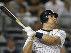 Yankees first baseman Mark Teixeira follows through on a two-run home run during the sixth inning against the Rangers Wednesday night in New York. Teixeira hit two-run home runs from both sides of the plate as the Yankees beat the Rangers 12-4.