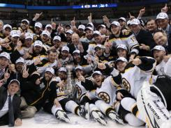 The Boston Bruins pose with the Stalney Cup after winning the franchise's first title since 1972.