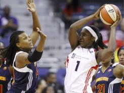 Mystic's' Crystal Langhorne (1) looks to pass the ball as Sun's Tina Charles (31) defend during the first quarter of Thursday's game in Washington. The Sun defeated the Mystics 79-71.