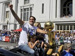 Mavericks owner Mark Cuban, with his daughter Alyssa, rides with the NBA Championship basketball trophy during the team's victory parade in downtown Dallas.