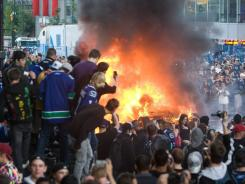 Fans in Vancouver watch a car burn following the Canucks' loss in Game 7 of the Stanley Cup Final.