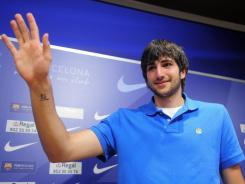 """Spanish basketball player Ricky Rubio waves during a news conference in Barcelona, Spain on Friday. Rubio is joining the Minnesota Timberwolves. The 20-year-old Spanish guard ended two years of speculation on Friday when he said, """"I have finally decided to start the journey"""" to the NBA."""