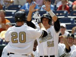 Connor Harrell (20) celebrates his home run with teammate Conrad Gregor (55) that broke a sixth-inning tie and sent Vanderbilt to a win in its first College World Series game.