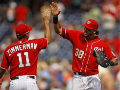 The Washington Nationals' Ryan Zimmerman, left, and Michael Morse  celebrate after beating the Baltimore Orioles 4-2 in Washington on  Saturday.