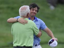 U.S. Open champion Rory McIlroy shares a moment with his day, Gerry McIlroy, following his record-setting win.