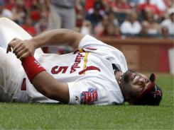 Albert Pujols grabs his left wrist after being injured on a play at first base.