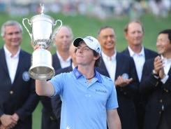 Rory McIlroy, trophy in hand, acknowledges the cheers after his Sunday walk in the park in the final round of the U.S. Open at Congressional Country Club in Bethesda, Md.