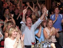 Members of Holywood golf club in Northern Ireland celebrate after watching Rory McIlroy win the U.S. Open on TV.