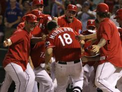 The Rangers mob Mitch Moreland after his 11th-inning, walk-off home run Tuesday night.