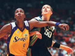 Los Angeles Sparks center Lisa Leslie, left, and the New York Liberty's Rebecca Lobo battle for rebound during the WNBA's first game on June 21, 1997.