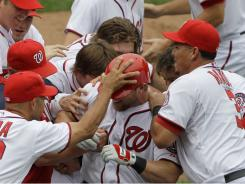 Laynce Nix, center, is mobbed teammates after driving in the winning run to defeat the Mariners 1-0.